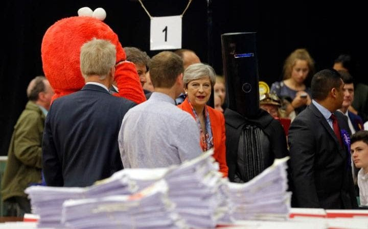 Theresa May, center, stands next to candidate 'Lord Buckethead' waits for the declaration at her constituency to be made for the general election in Maidenhead, England