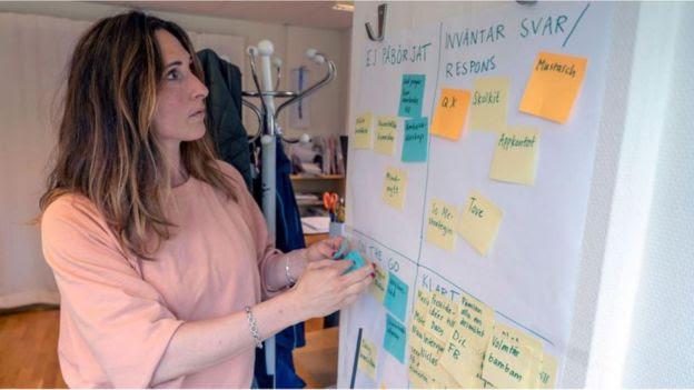 Selene Cortes em frente a um quadro com notas