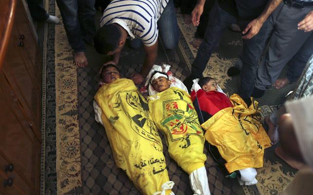 Los cuerpos de tres niños palestinos que murieron a causa de un proyectil israelí.