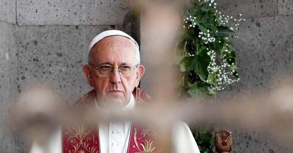 papa francisco serio mirando por una cruz