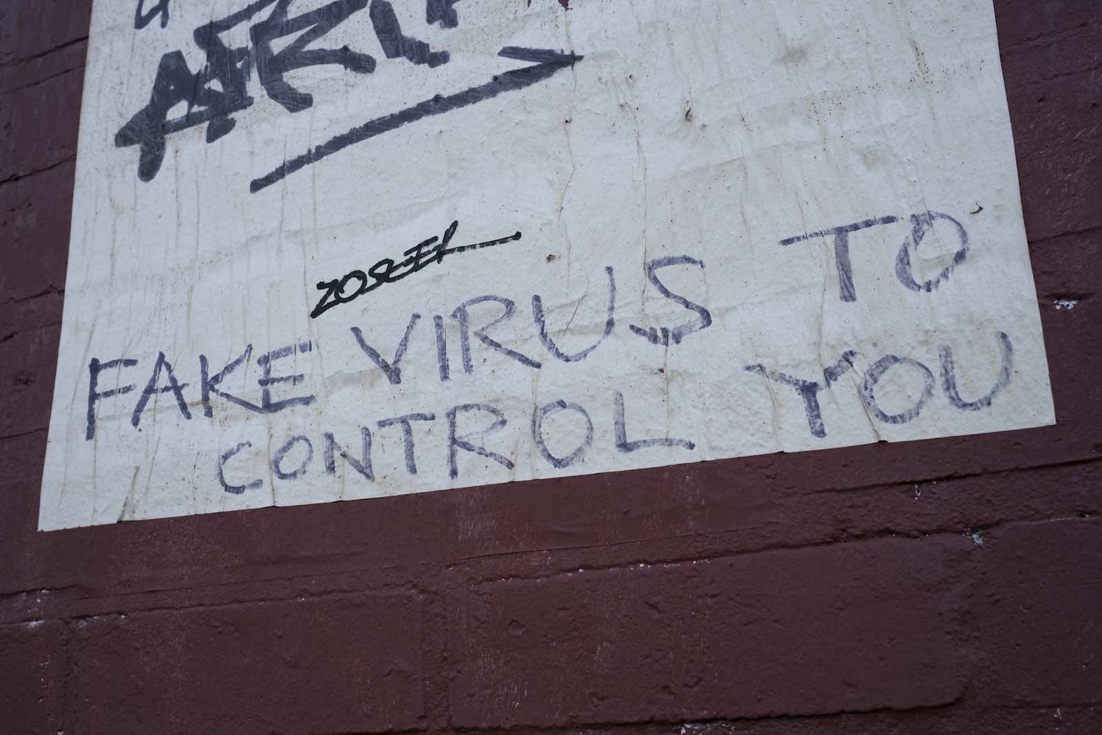 """Graffiti on the side of a building that says """"fake virus to control you"""""""