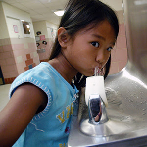 student drinking at                                           school water fountain
