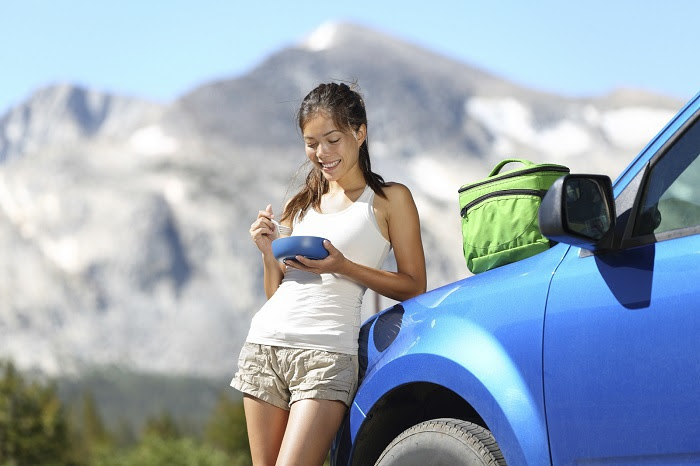 Road Rules for Food Safety, image of young women eating beside her car outdoors.