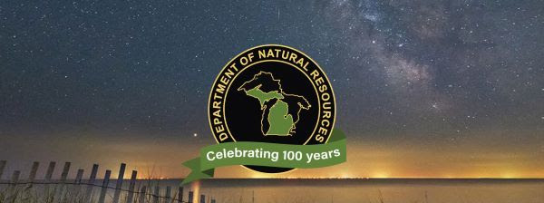 Banner image of DNR centennial logo against a starry sky