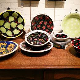 Hand-made ceramic bowls in vibrant colors and patterns including: green pears on a black background; yellow sunflowers on a blue background; red holly berries and green leaves on a black background; mixed jewel-colored vegetables on black background; and white bees on a light green background.