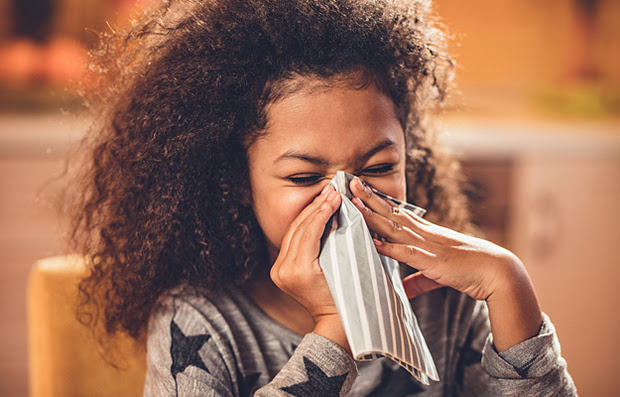A young girl with the flu blowing her nose.