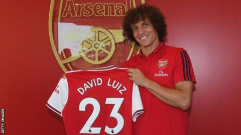 David Luiz holds an Arsenal shirt