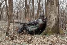 turkey hunter sitting against a tree