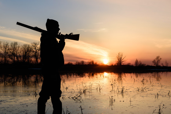 A hunter holding a gun over his shoulder at sunset by the water.
