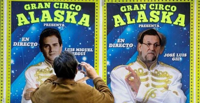 Un hombre toma una fotografía de los carteles de un circo que actúa estos días en Valencia y en los que alguien ha sustituido las caras de dos de sus artistas por los candidatos a la presidencia del Gobierno Albert Rivera y Mariano Rajoy./ EFE