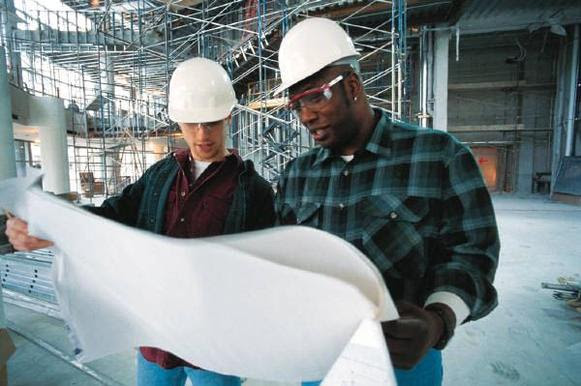 Photo: Two construction workers looking at plans on a construction site.
