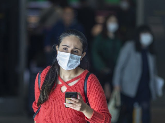 LOS ANGELES, CA - FEBRUARY 02: Travelers arrive to LAX Tom Bradley International Terminal wearing medical masks for protection against the novel coronavirus outbreak on February 2, 2020 in Los Angeles, California. The United States has declared a public health emergency and will implement strict travel restrictions later today. Foreign …