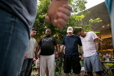 People praying for the Dallas shooting victims at Klyde Warren Park in Dallas on Saturday evening.