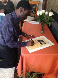 Signing President Sata's book of condolences at Mr & Mrs Mate's residence in Cochrane, AB, Canada