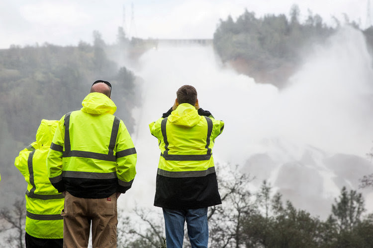 A crew monitors water flowing through a damaged spillway on the Oroville Dam. (Reuters/Max Whittaker)</p>