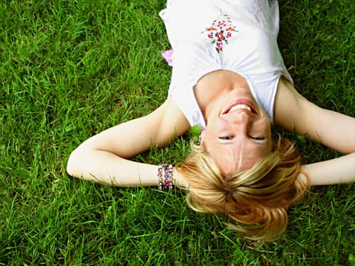 A similing woman lying on a green field