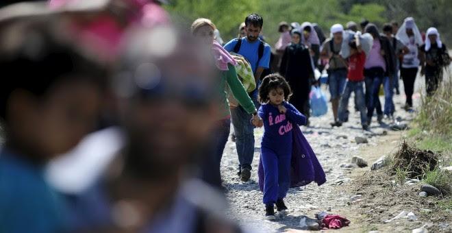 Los migrantes caminan hacia un campo de refugiados en Gevgelija, Macedonia, después de entrar en el país por el cruce de la frontera con Grecia. REUTERS