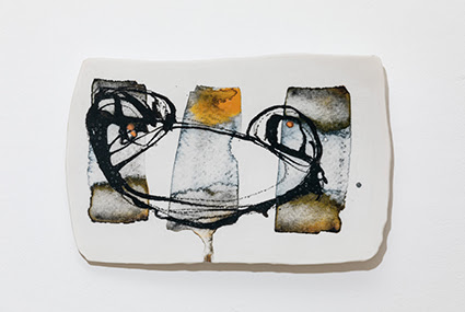 A photograph of a ceramics plate by Jennifer Alford. The object is white with black, grey, brown and yellow abstract drawing on, and it is displayed against a solid white background.