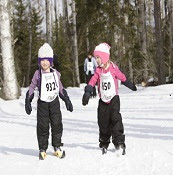 Two young girls cross-country skiing