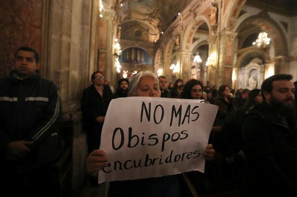 Una manifestante sosteniendo un letrero durante una misa en Santiago este mes