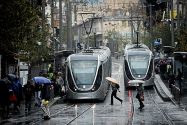 rain People carry umbrellas to protect themselves from the rain as they cross Jaffo Street, on a winter day in the center of Jerusalem.jpg