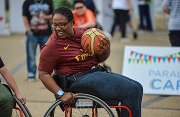 A woman in a wheelchair basketball chair with a ball in her hands