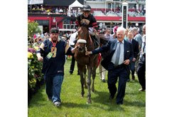 Frank Stronach (right) leads Shaman Ghost into the winner's circle at Pimlico Race Course