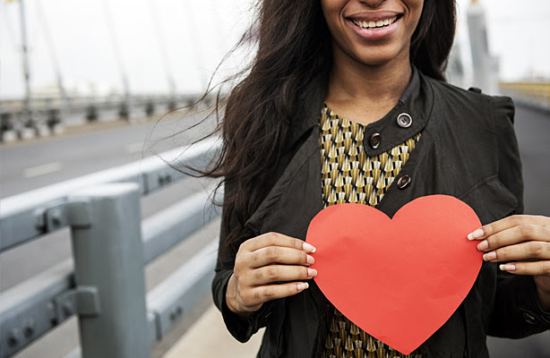 A woman holding a paper heart.