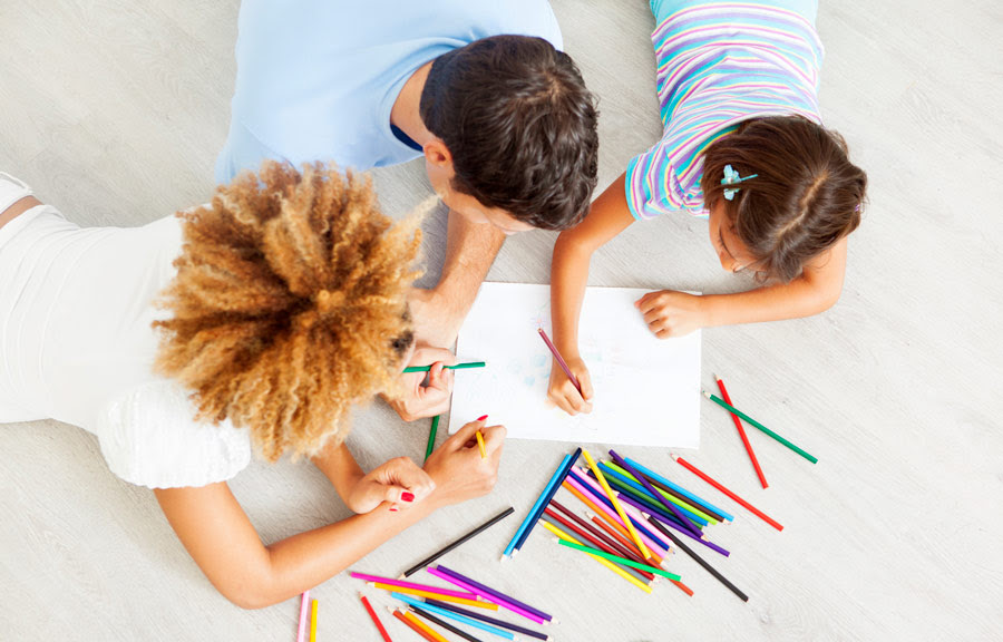Kids coloring on paper with colored pencils