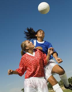 Girls Heading Soccer Ball During Match