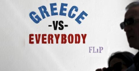 """Un hombre pasa junto a una pintada del artista callejero Flip, en Atenas, que dice """"Grecia contra todos"""". REUTERS/Alkis Konstantinidis"""