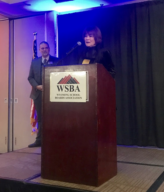 Judy speaks from a podium with a WSBA (Wyoming School Boards Association) sign on the front while WSBA Executive Director Brian Farmer observes.
