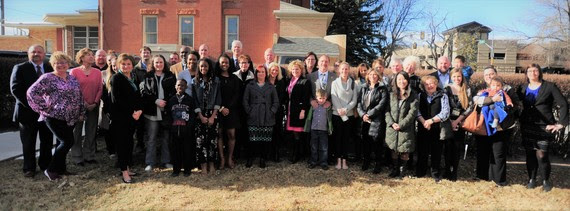 State Superintendent Jillian Balow and Governor Matt Mead pose for a photo behind the Governor's Office with several dozen people in support of adoption month.