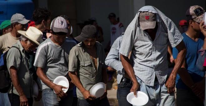 Integrantes de la caravana de migrantes centroamericanos que se dirigen a Estados Unidos hacen fila para recibir alimentos el municipio de Juchitán, en el estado de Oaxaca (México). - EFE