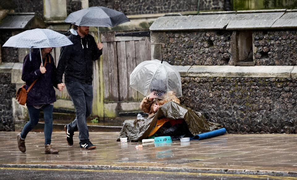 A man begs for money under an umbrella on the pavement during torrential rain in Brighton yesterday