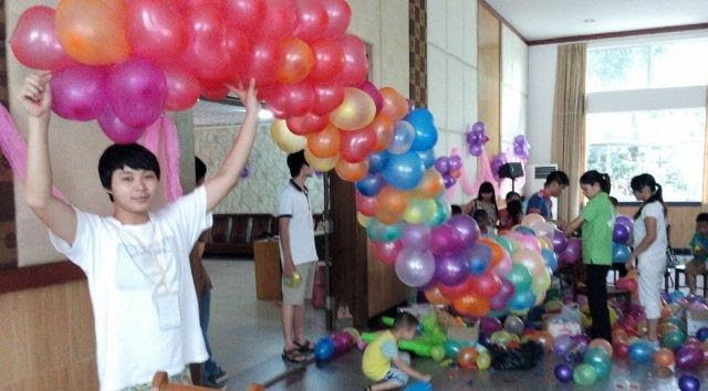这是我的同学,他叫周天明,我们正在把气球挂到墙上。This is my classmate. He is called Zhou Tianmin. We were preparing balloons to hang on the wall.