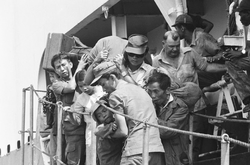South Vietnamese refugees disembark at Cam Ranh Bay in Vietnam, Saturday, March 30, 1975 on South Vietnam?s central coast following a voyage from Da Nang, the city which has since fallen to communist forces. Westerner at right is a member of the ship?s crew. (AP Photo/Nick Ut)