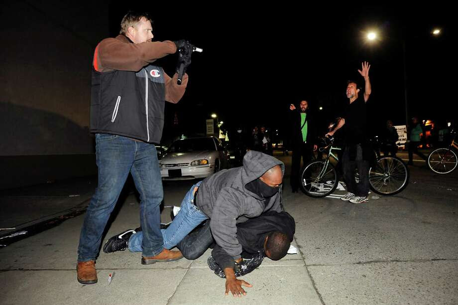 An under cover officer points his gun at the crowd while his partner subdues a protester who struck him in the back of the head, as demonstrations continue for a fifth night in Oakland on Wednesday, Dec. 10, 2014. Photo: Michael Short / Special To The Chronicle / ONLINE_YES