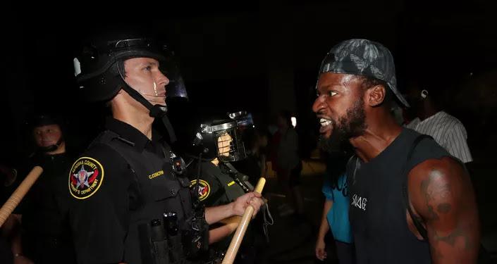 Un afroamericano confronta a un policía durante los disturbios en Kenosha, Wisconsin
