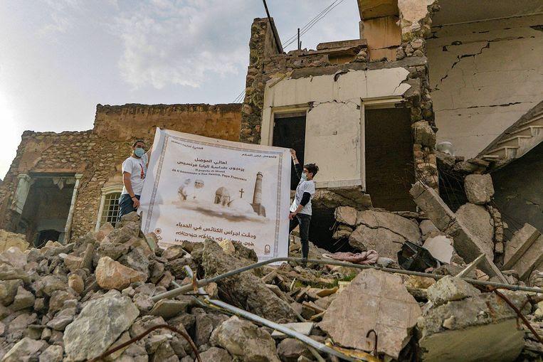 Iraakse jongeren halen een poster van de paus boven in Mosul. Beeld AFP