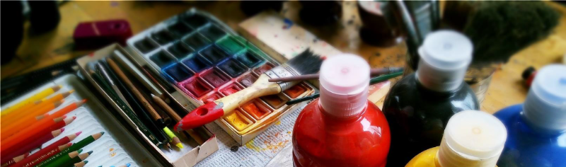 Colorful photos of paint_ brushes_ and colored pencils on a table