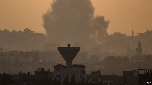 A picture taken on 20 July 2014, from the southern Israeli-Gaza border shows smoke billowing from buildings following an Israeli air strike on Gaza City.