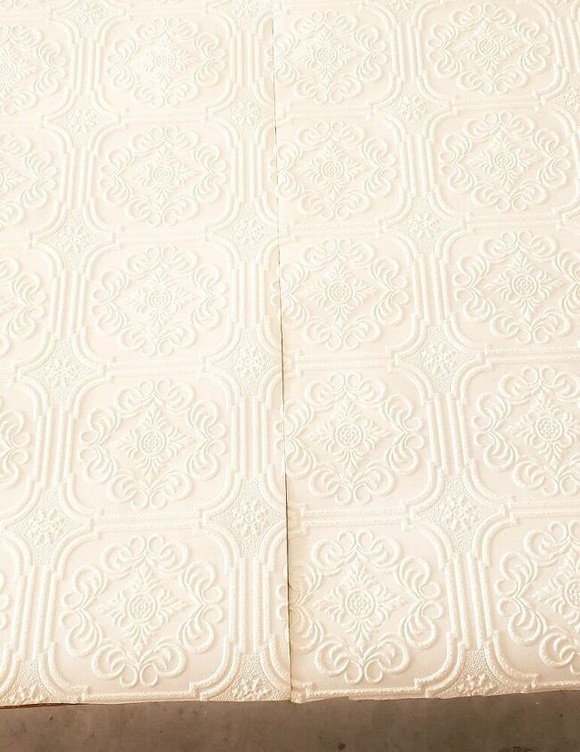 White patterned wallpaper cut down middle.
