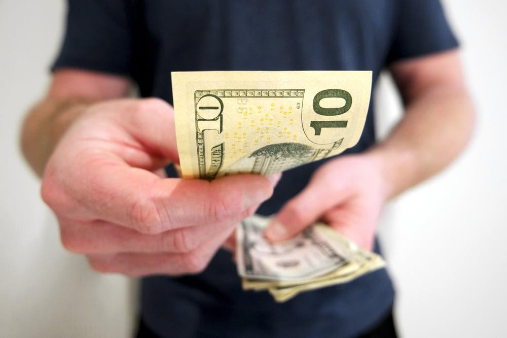 Man handing over a ten dollar bill