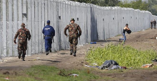 Un migrante cruza la frontera de Hungría mientras soldados y policías tratan de atraparlo. REUTERS