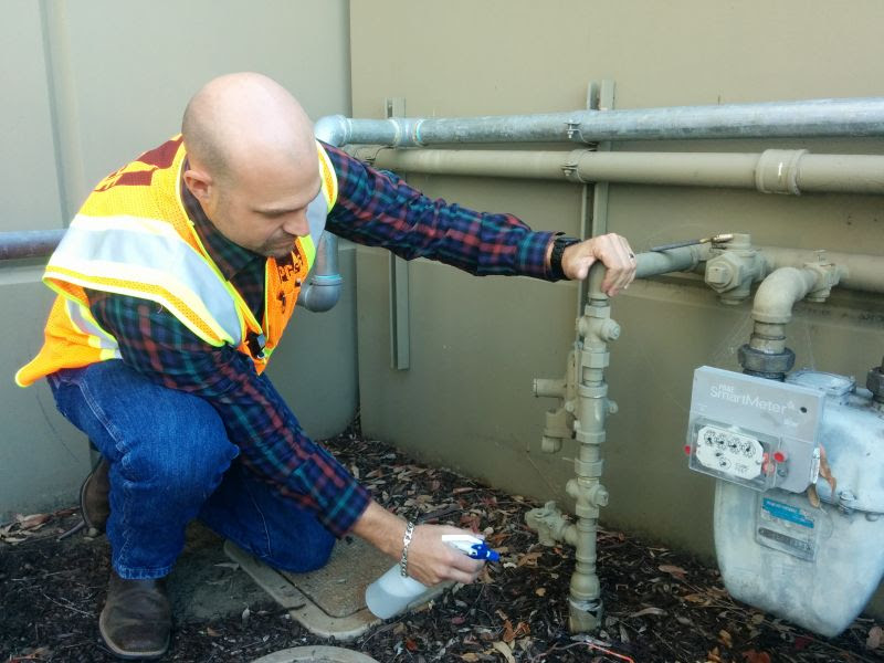 A PG&E crew member uses soap to identify the exact location of a gas pipeline leak.