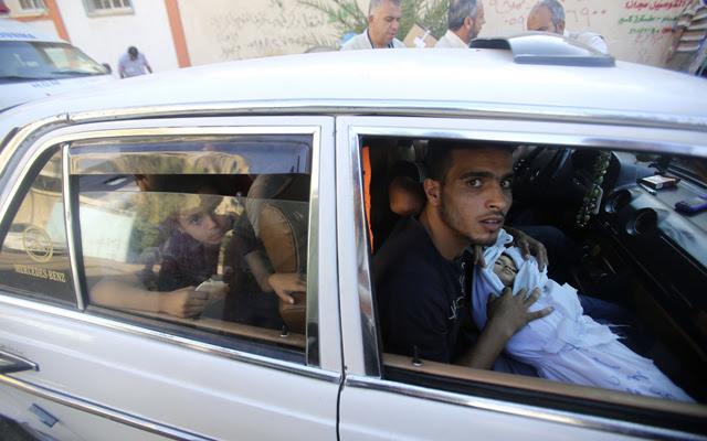 Los familiares de dos niños menores de tres años fallecidos en un bombardeo israelí transportan sus cuerpos en la ciudad de Rafah, este lunes 4 de agosto.