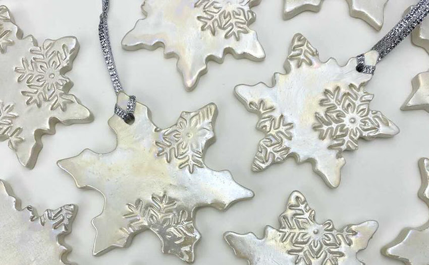 A photograph of star-shaped silver christmas ornaments. The ornaments have a shiny silver glaze on and are imprinted with snowflake motifs.