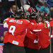 Canada's women's hockey team celebrates Marie-Philip Poulin's game-winning goal.