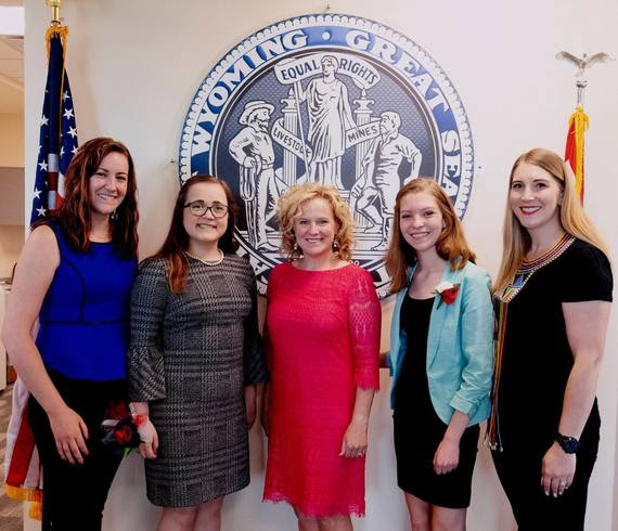 From left-to-right: WDE Communications Director Kari Eakins, Girls State delegate Riley, State Superintendent Jillian Balow, Girls State delegate Bailey, and WDE Chief Policy Officer Megan Degenfelder stand in front of the Great Seal of the State of Wyoming at the WDE.